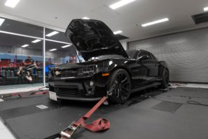 A black Mustang GT with tinted windows sitting in a garage with its front hood lifted